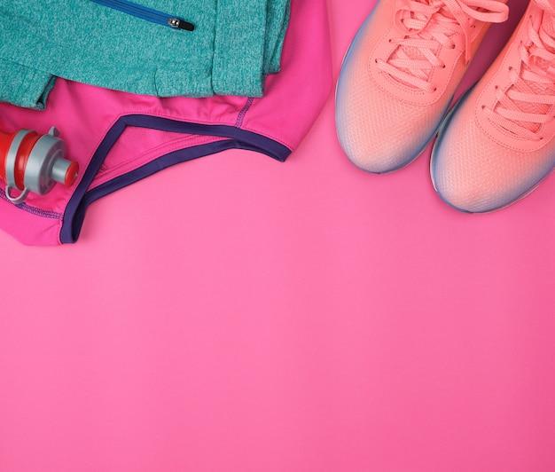 Спортивная одежда, обувь и пресная вода в бутылке на розовом фоне