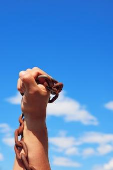 男性の手はさびた金属チェーンを保持します