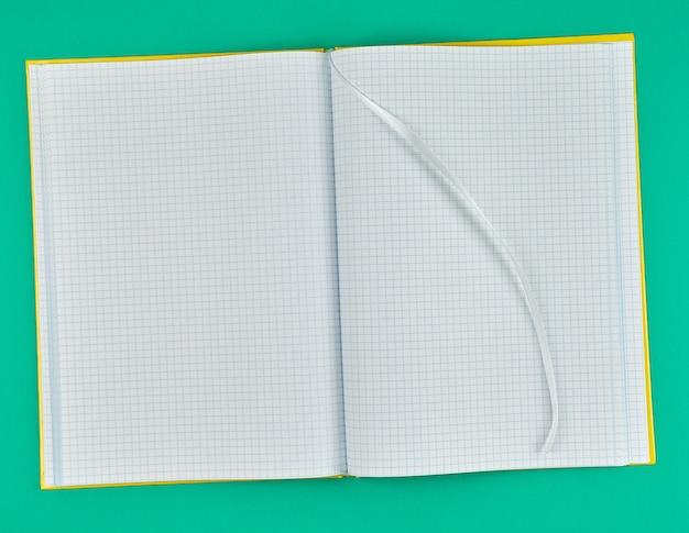緑の背景に沿ってノートブックを開く