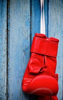 木製の青い表面にぶら下がっている赤いキックボクシンググローブ