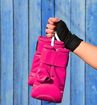 女性の手でキックボクシングのための革のピンクの手袋