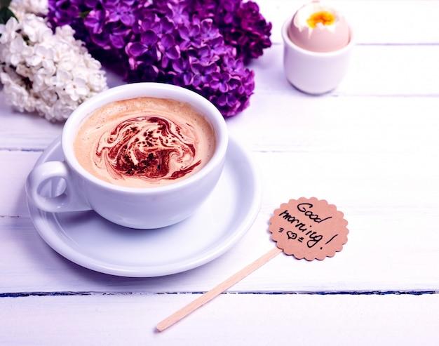 白い木製の背景にカプチーノのカップ