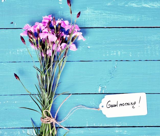 ピンクのカーネーションと紙タグの花束