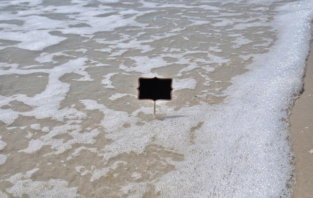 海岸に空の黒いプレート