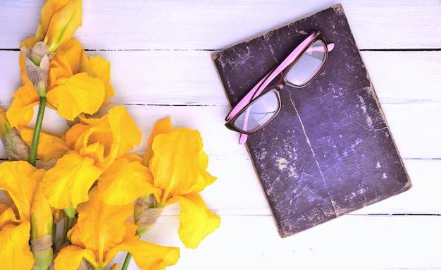 白い木製の背景上の眼鏡の古い本