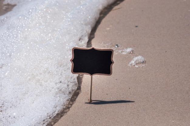 空の木製の黒い看板がビーチ