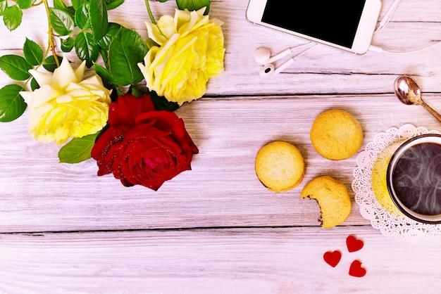 Горячий кофе в желтой кружке, печенье и мобильный телефон