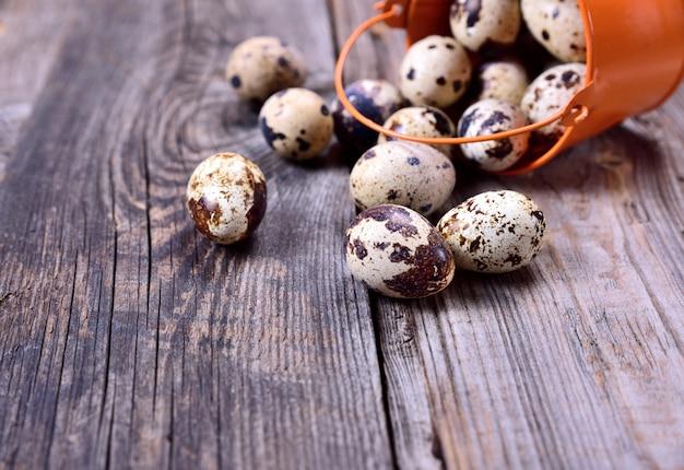 灰色の木製の背景に生のウズラの卵
