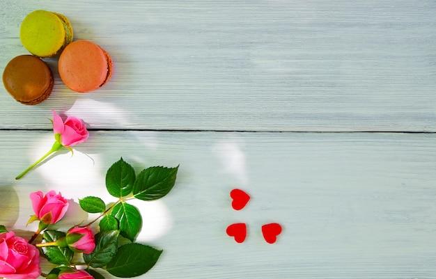 白い木製の背景とピンクのバラの花束