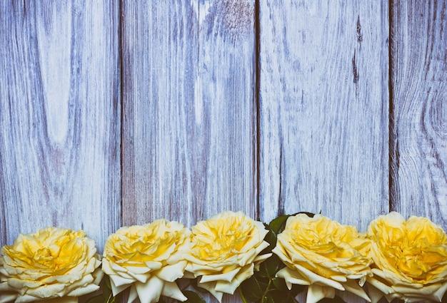 白い木製の背景に黄色のバラの花束
