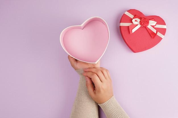Две руки держат бумажную открытую красную коробочку в форме сердца