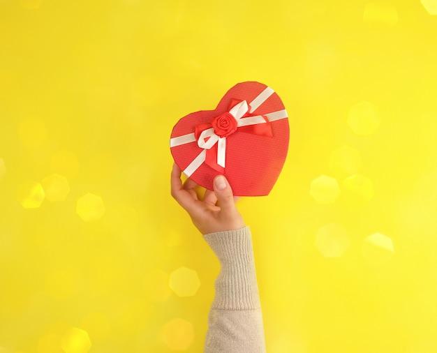 片手でハートの形をした紙で閉じた赤い箱