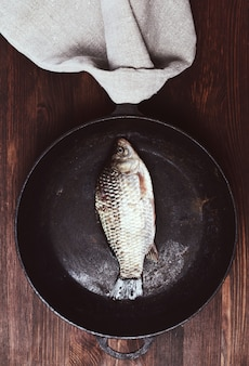 黒のフライパンで新鮮な魚の鯉
