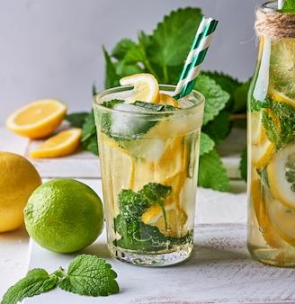 Летний освежающий напиток лимонад с лимонами, листьями мяты, лаймом в стакане