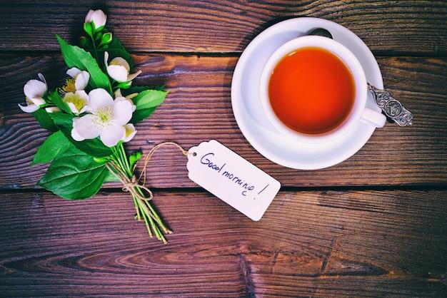 一杯の紅茶と紙のタグと開花ジャスミンの花束