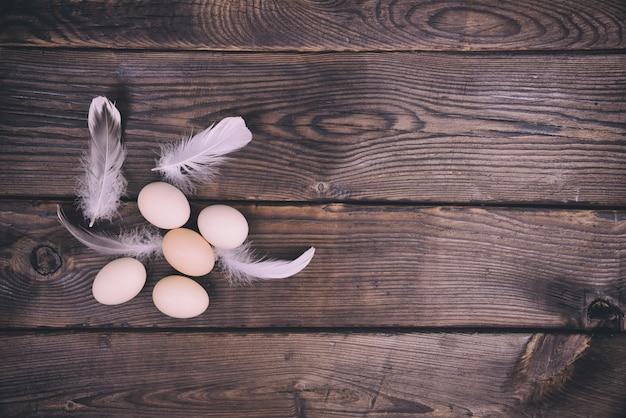 茶色の木の表面に鶏の卵のグループ