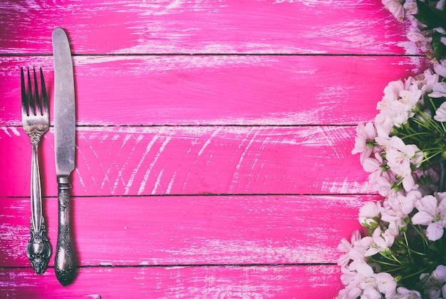 鉄のフォークとナイフ、ピンクの木製の背景