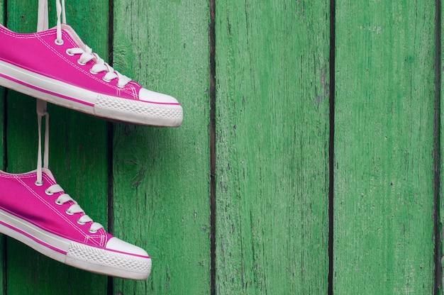 ひびの入った木製の壁に掛かっている明るいピンクのスポーツスニーカーのペア