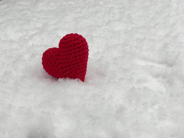 白い雪の上に横たわる小さな赤いニットハート