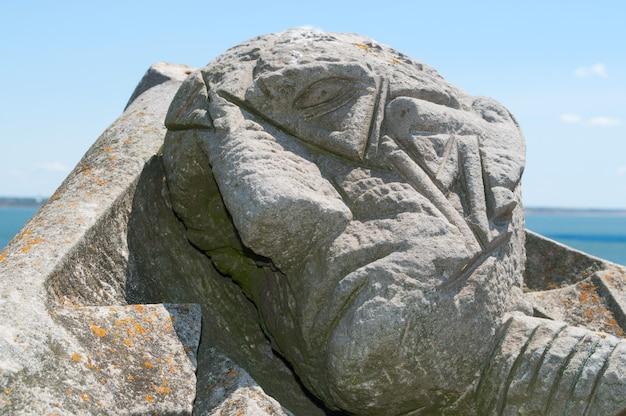 Каменная голова человека крупным планом на фоне неба