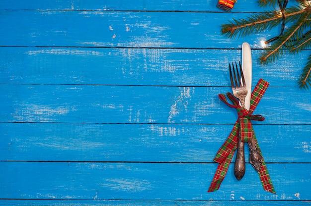 フォークとナイフ、青い木製の背景にリボンで縛ら