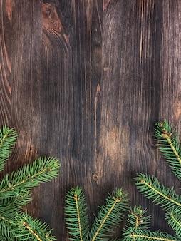 木の板の背景に緑のモミの木の枝