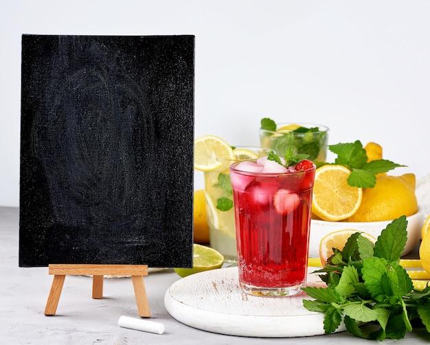 夏の飲み物のレシピとベリーレモネードのガラスを書くための空の黒いチョークボード