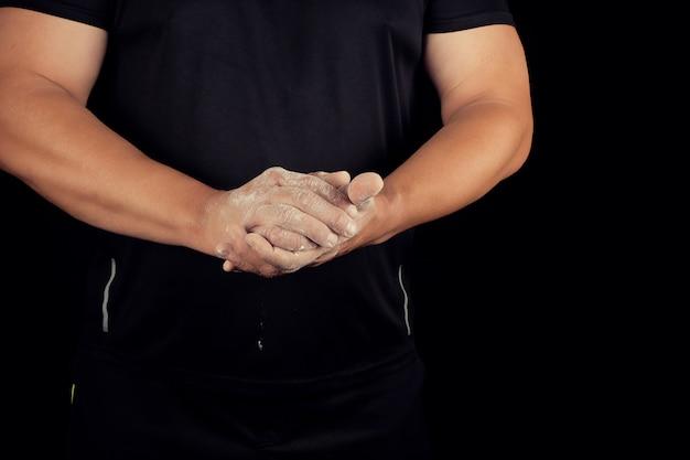 スポーツイベントの前に成人男子アスリートがマグネシアで白い粉をこすります
