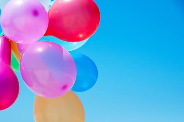 青い空を背景に色とりどりの風船