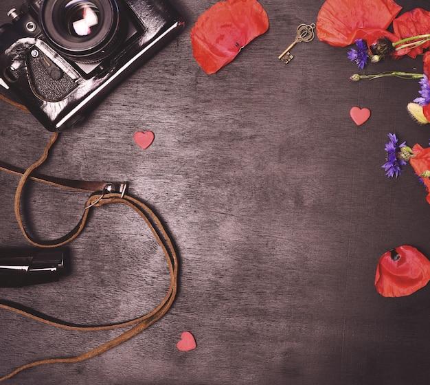 古いビンテージ写真カメラと赤いケシの花束