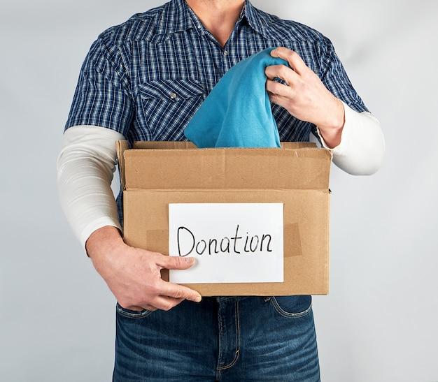 青い市松模様のシャツとジーンズの男は大きな茶色の紙箱を保持します