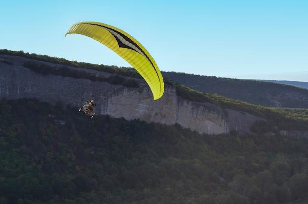 パラグライダーが山の上を飛んで