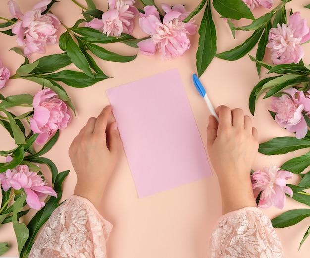 女性の手が空のピンクの紙のシートの上に白いペンを手を握ってください。
