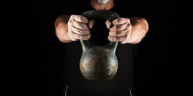鉄のケトルベルを保持している黒い服を着た大人の強い運動選手