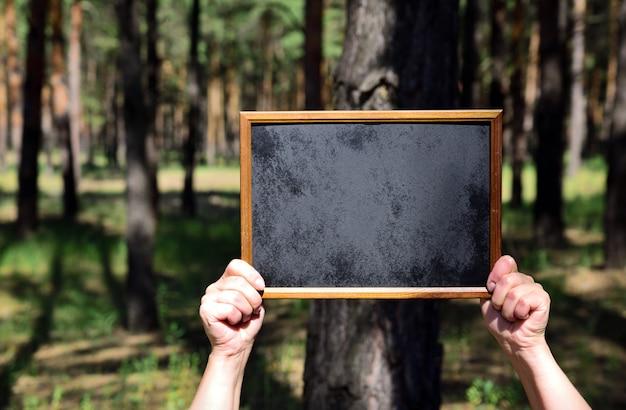 人間の手、黒の空の木製表面フレームを保持