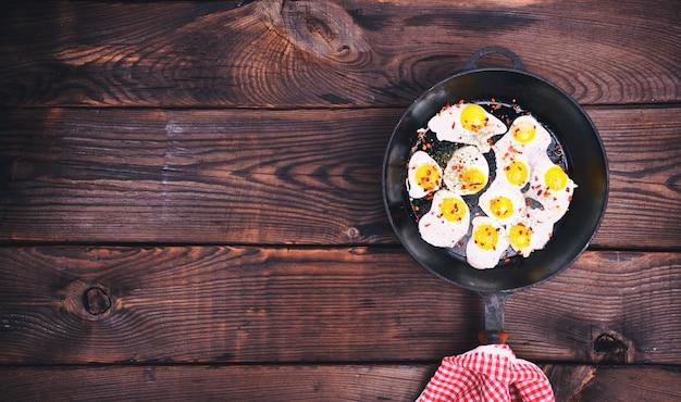 鋳鉄製の黒いフライパンで揚げられたウズラの卵