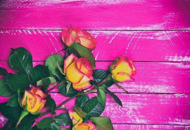 ピンクの木の表面に黄色いバラの花束