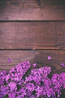 茶色の木の表面に白いライラックの花束