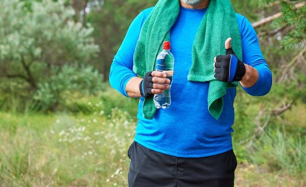 大人の運動選手は緑のタオルで青い制服を着た自然の真ん中に立っています。
