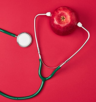 Спелый яблочный и зеленый медицинский стетоскоп