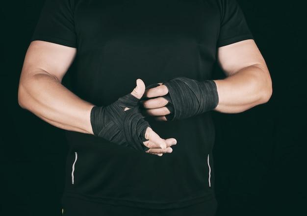 運動選手は黒い服を着て立って、繊維弾性包帯で彼の手を包みます