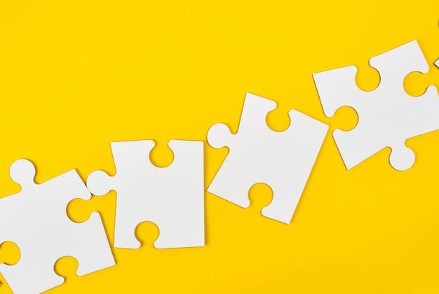 黄色の背景に空白の白い大きなパズル
