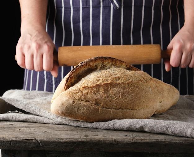 エプロンの女性は焼き丸パンの横にある木製の麺棒を保持します。