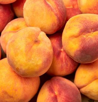 Куча спелых желто-красных круглых персиков