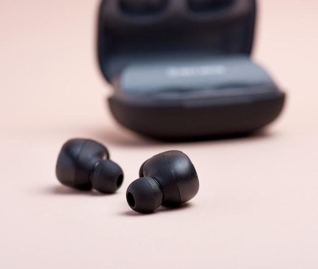 黒いワイヤレスイヤホンと充電ボックスのペア