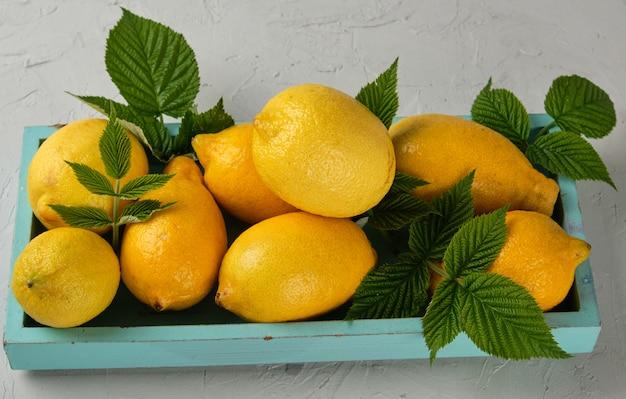 青い木製ボード上の新鮮な熟した全黄色レモン