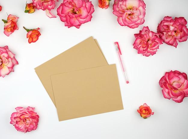 ピンクのバラのつぼみと茶色の紙の封筒