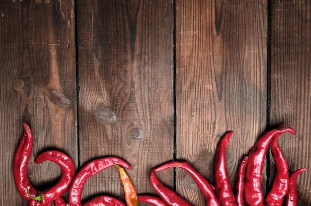 ボードから茶色の木製ビンテージ背景に熟した赤唐辛子