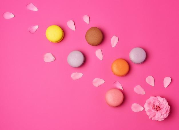 Разноцветные макаруны со сливками и розовым фоном с бутонами роз с разбросанными лепестками