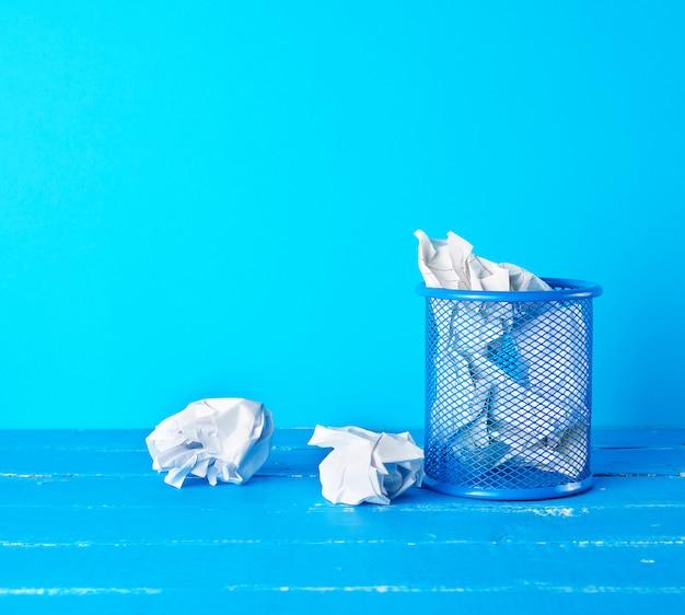 しわくちゃの白い紙で満たされた青い金属製のバケツ